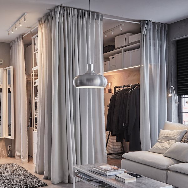 An open wardrobe solution, light grey GUNRID curtains, a black clothes rack and a white sofa with grey cushions.