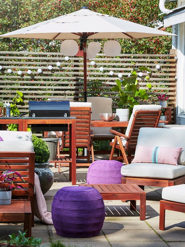An outdoor space, furnished with outdoor tables, chairs and a parasol, with cushions and pouffes and lighting.
