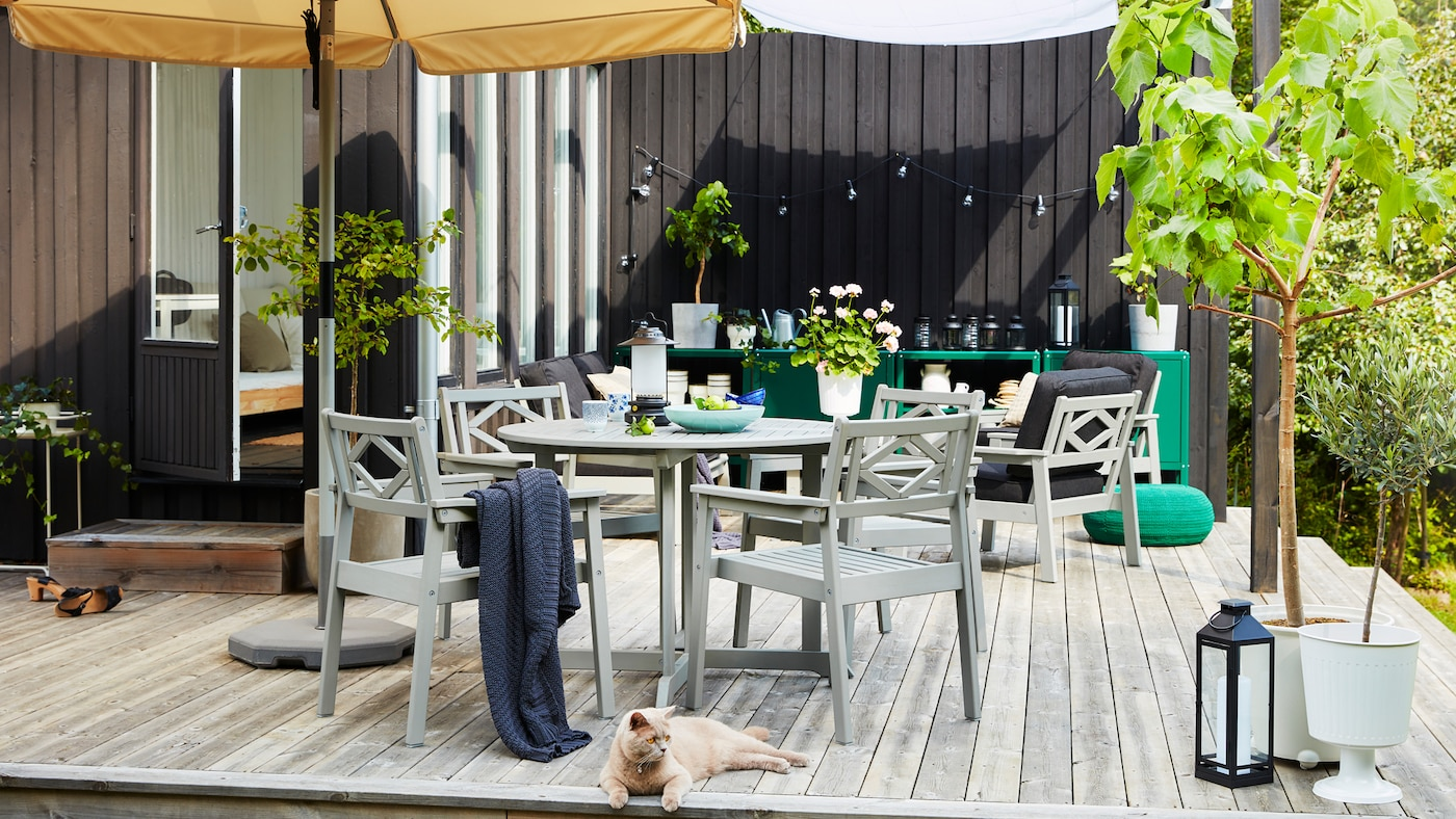 An outdoor space on a wooden deck with a beige parasol, grey outdoor furniture, green planted trees and a cat.