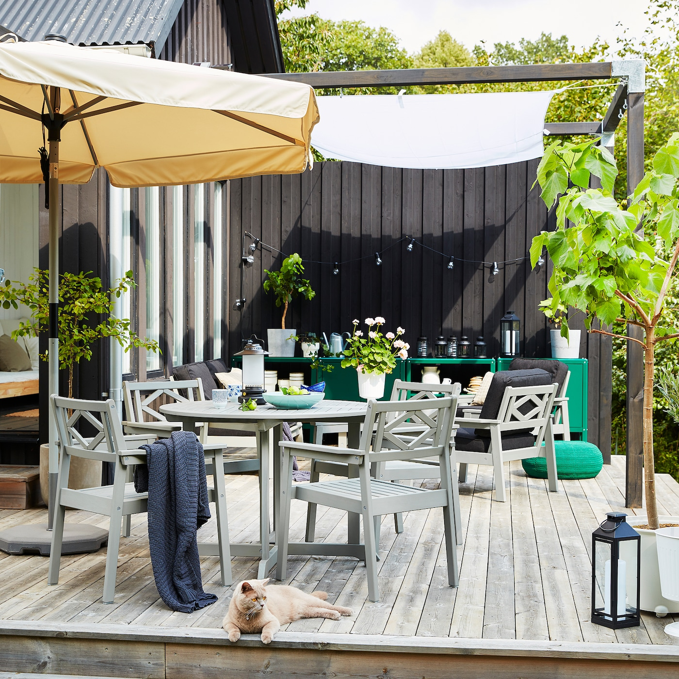 An outdoor space on a wooden deck with a beige parasol, grey outdoor furniture, green planted trees and a grey/orange cat.