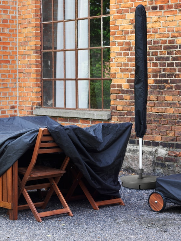 An outdoor table and chairs in wood, stored under a black cover beside a brick building with a window and furled parasol.
