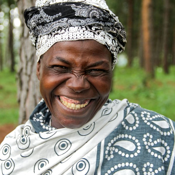 An Ugandan woman, broadly smiling, who's involved in the White Nile project.