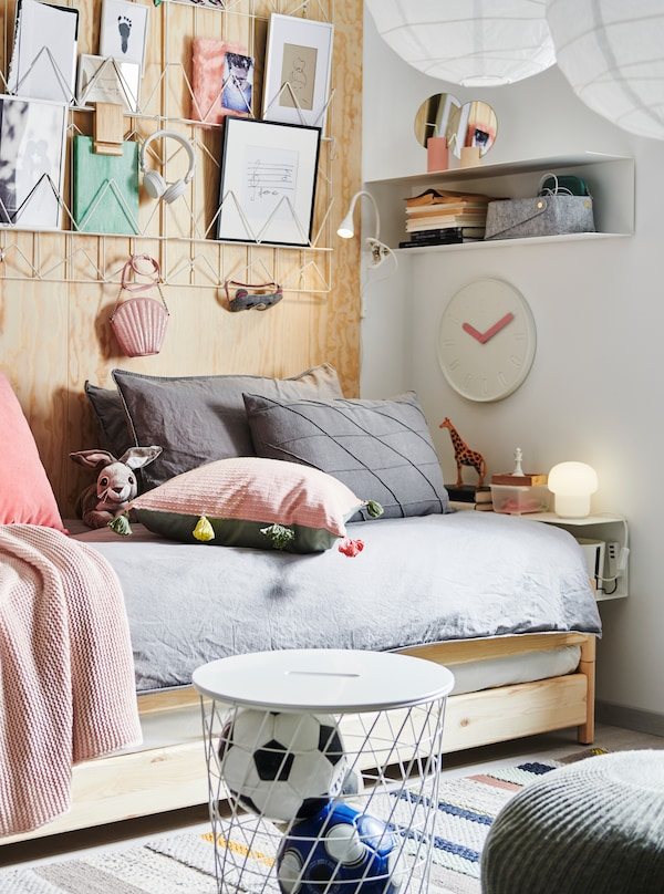 An UTÅKER stackable bed with lots of cushions on, paper art above, a bedside BOTKYRKA shelf, storage and decorations.