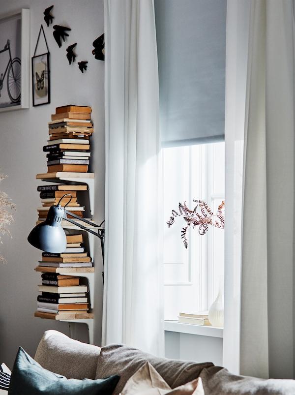 安装了半透明白色窗帘和灰色百叶卷帘的窗户,旁边是一列的二手书和一盏阅读灯。