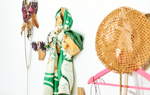 Asymmetric bamboo hooks on a wall, each with a different clothing accessory – sunglasses, a scarf, necklaces and a straw hat.