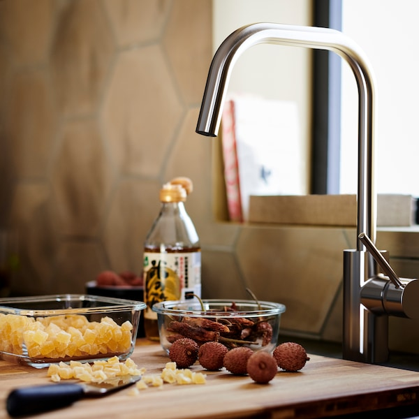 Brown wood chopping board with two glass containers, beneath an ÄLMAREN kitchen mixer tap in stainless steel colour.
