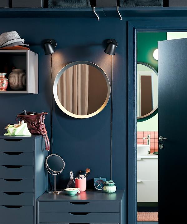 把浴室外的空间被布置成了简约的化妆台,设有镜子、抽屉柜和化妆品。