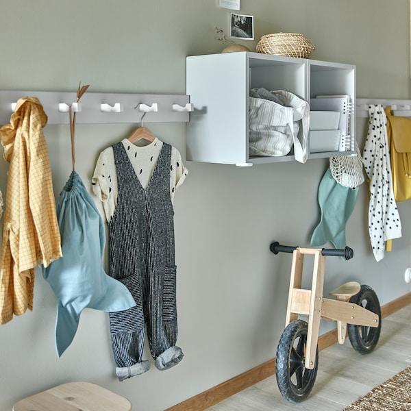 白色壁式多钩衣帽架上挂有儿童衣物,浅灰色搁架单元和木质儿童自行车。