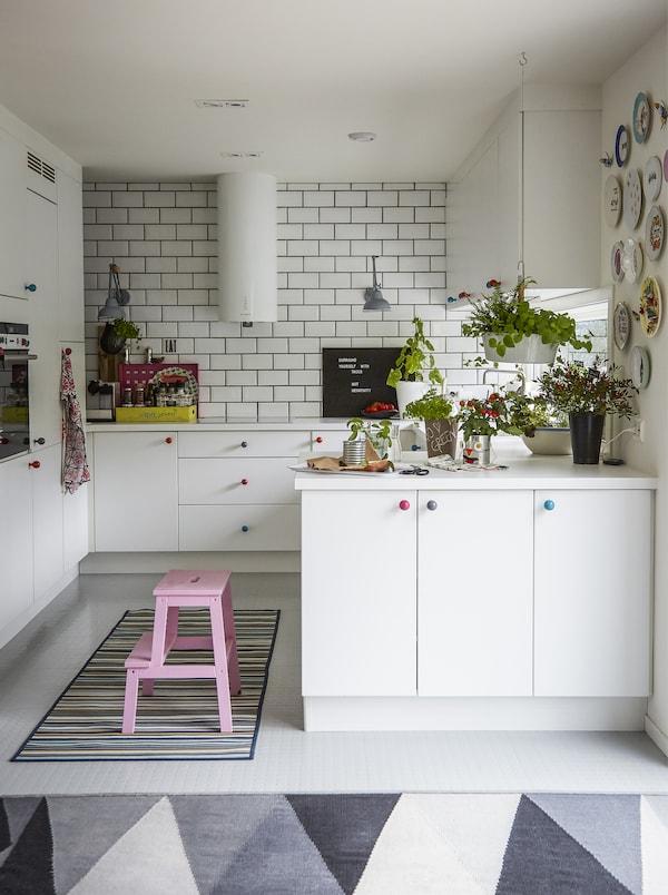 白色厨房内配有彩色踏脚凳和地毯。