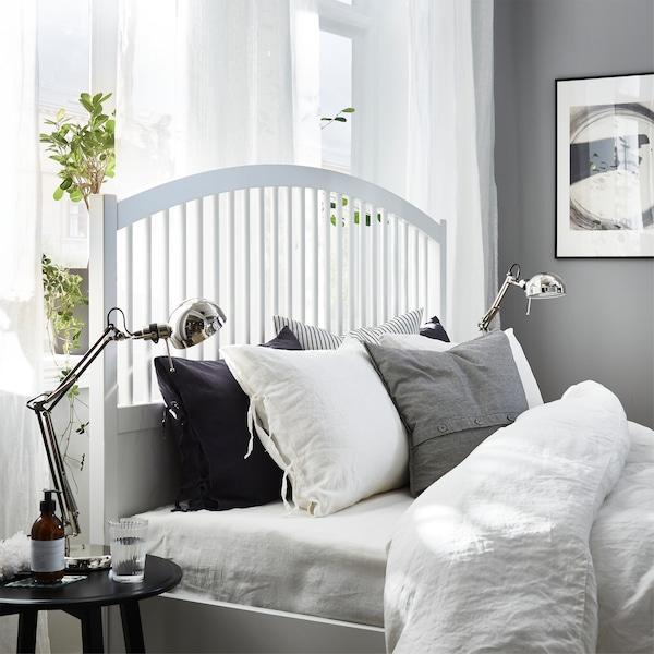 白色床架、白色窗帘、白灰黑色的床用纺织品和镀镍工作灯。