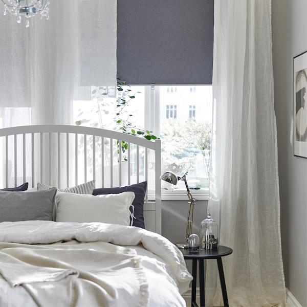 白色床架、白色窗帘、灰色遮光卷帘、枝形吊灯和黑色套桌。
