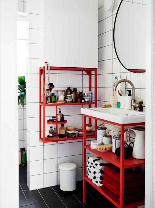 白色瓷砖的浴室里,配有红色和白色的ENHET 安纳特 模块单元,存放着装饰品和配饰。