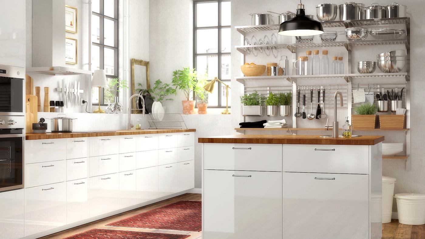 白色大厨房,带独立橱柜和白色高光柜门,搭配橡木工作台和一套开放式悬挂搁架。