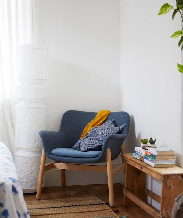 白色的房间里,蓝色扶手椅位于角落,此外还有一盏带有纸质灯罩的落地灯。