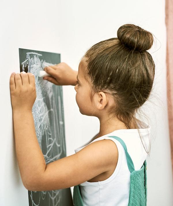 白色的墙壁上有一块黑板墙壁不干胶即时贴,一个女孩正用粉笔在上面作画。
