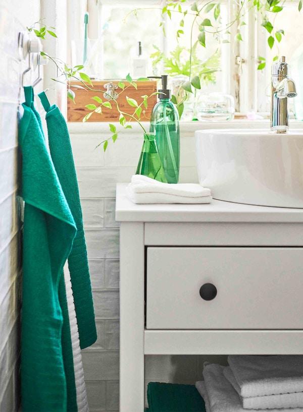 白色的洗脸池柜上放着鲜绿色瓶子和花瓶,左边挂着两条绿色毛巾。