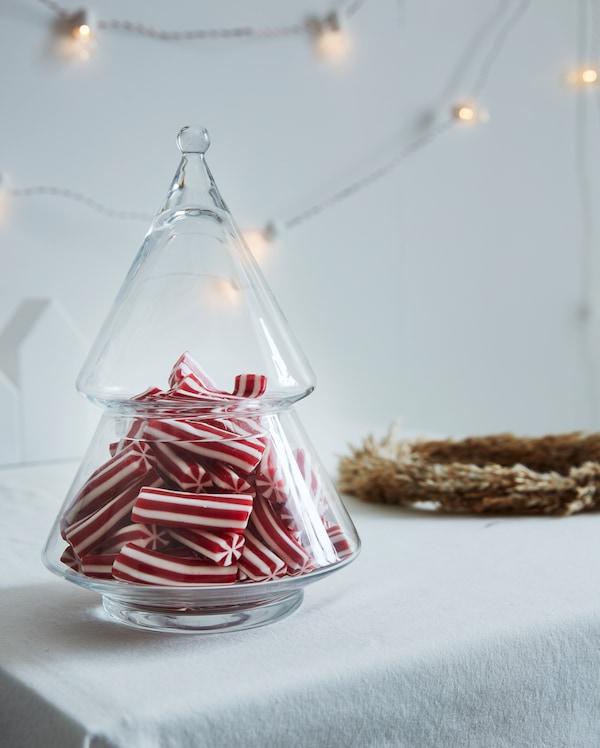 白色的桌布上放置着洁净透明的 VINTERFEST 温特菲斯 玻璃上菜碗,装满了红色和白色条纹的糖果。
