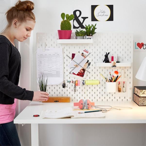 白色洞洞板上的搁板可用来放置小盆栽,笔筒可用来盛笔等文具,还可将时间表用夹子夹在洞洞板上。