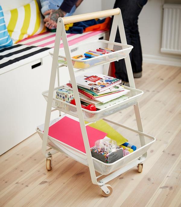 白色手推车上安着三个篮子,里面装满了彩色铅笔、书本和纸张。