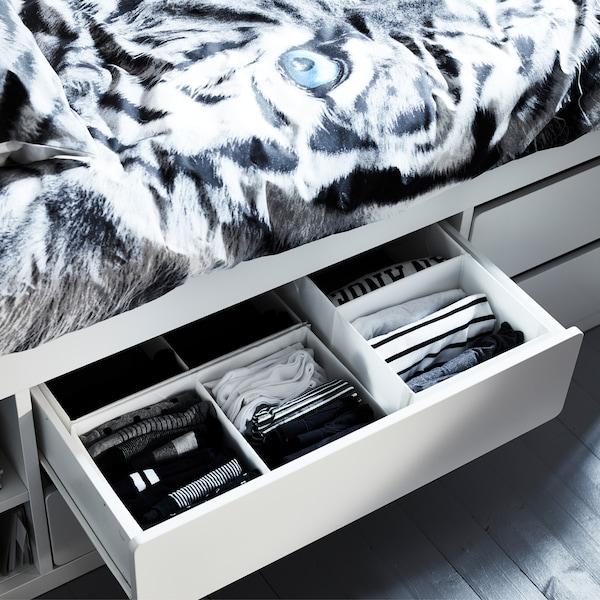 白色 SLÄKT 斯莱克 带抽屉床架内的开放式抽屉内放着整整齐齐的衣服。