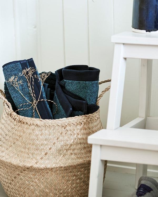 白色踏脚凳边放着一个采用天然材料织成的篮子,里面装满了卷起来的蓝色毛巾。