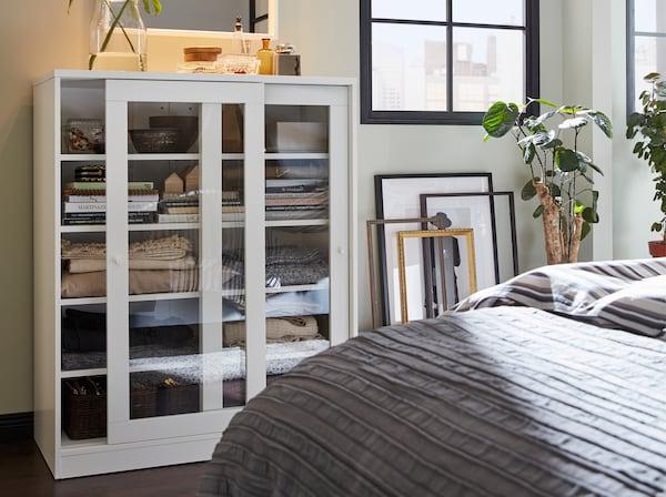 白色推拉玻璃门柜子,储藏柜框架靠墙而立,还有一套灰色的床罩。
