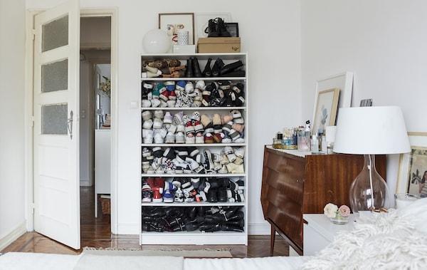 白色卧室里铺着木地板,鞋子叠放在书架上。