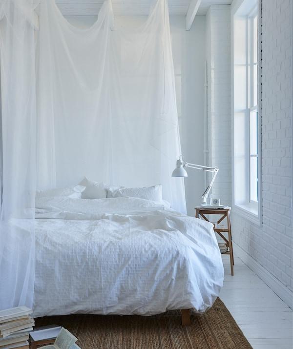 白色卧室内配有白色的床上用品,床边围着轻薄的白色挂帘。