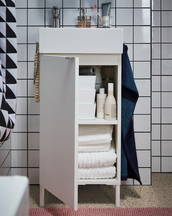 白色洗脸池柜内放有毛巾,地板上铺有粉色浴室地垫,柜子侧边放有深蓝色毛巾。