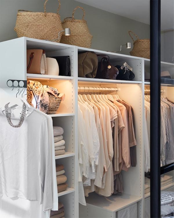 白色衣柜带镀镍橱柜照明、挂衣杆和海草编织篮子。