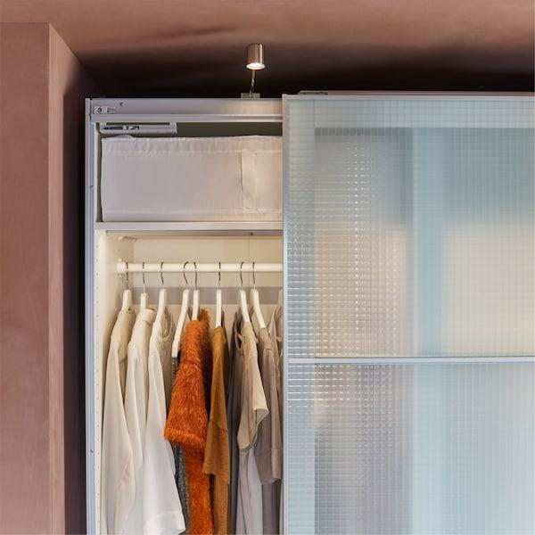 白色衣柜带格纹图案和毛玻璃柜门、柜灯和白色挂衣架。