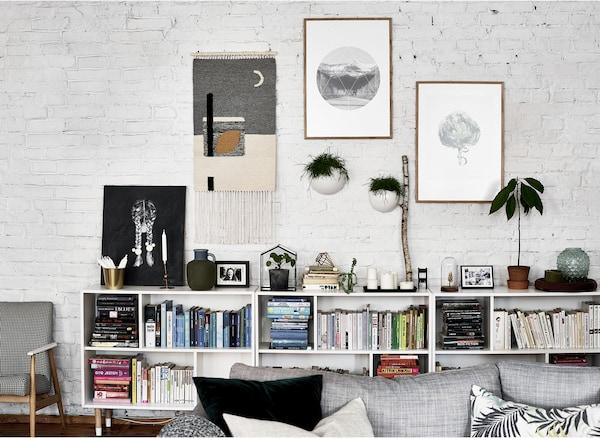 白色砖墙上挂着艺术品,低矮的搁架单元上摆放着书和植物。
