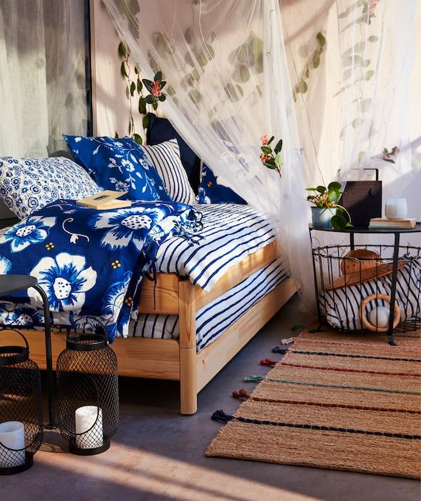 白天,阳台上的两张 UTÅKER 于托克 床具堆叠成沙发造型,上面摆放着枕头和靠垫。