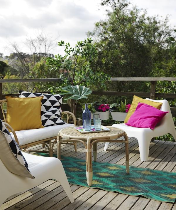 摆放着藤条沙发和桌子、塑料扶手椅、彩色地毯和靠垫的平台区域。