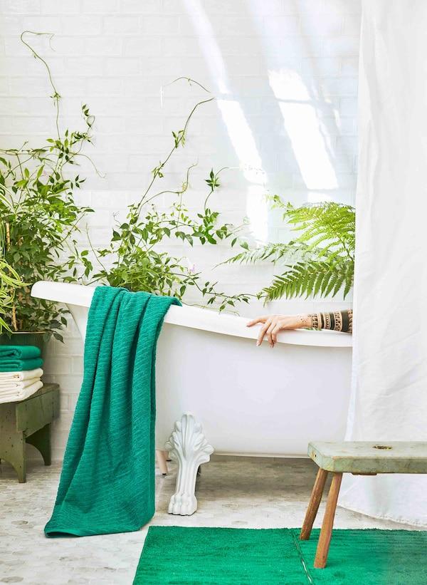 摆满绿植的浴室里放着白色浴缸,半掩在白色窗帘下。