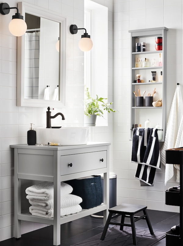 Bathroom with grey HEMNES one-drawer washstand, HEMNES wall shelf with towels, a HAMNSKÄR mixer, a mirror, and two lamps.