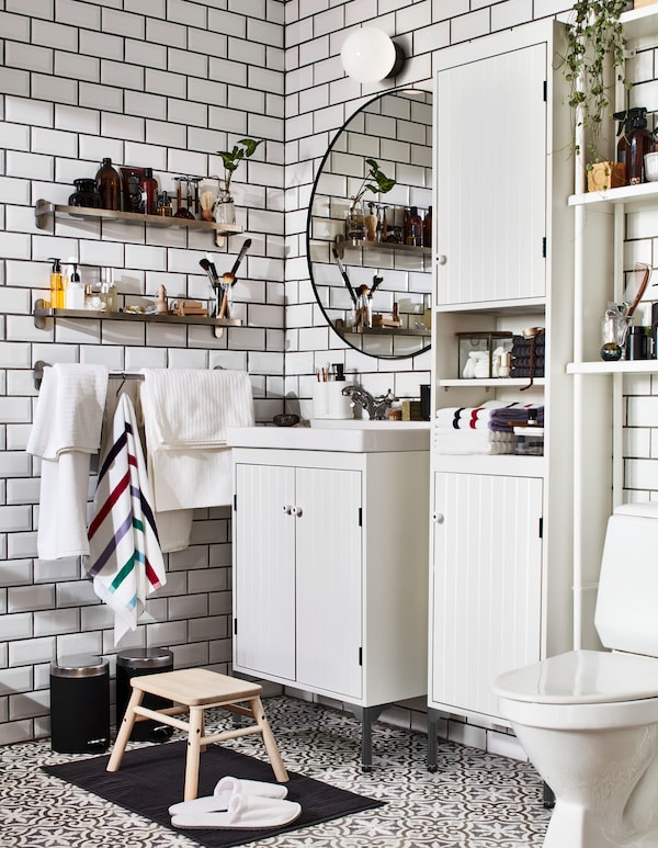 Bathroom with white SILVERÅN washstand and cabinets, and wall-mounted BROGRUND glass shelves: one for him and one for her.