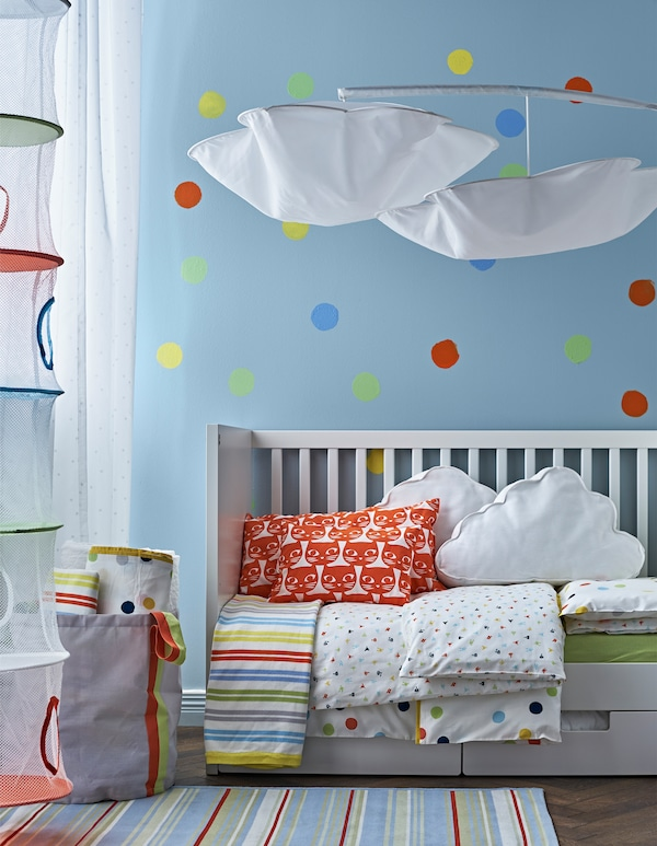 Bed textiles, a rug and a polka dot painted wall in primary and secondary colours that make it easy to go from a nursery to child's room