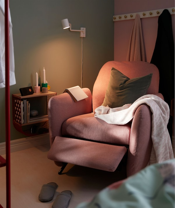 Bedroom corner between bed and a room divider with a recliner, wall-mounted reading light and a small wall shelf.