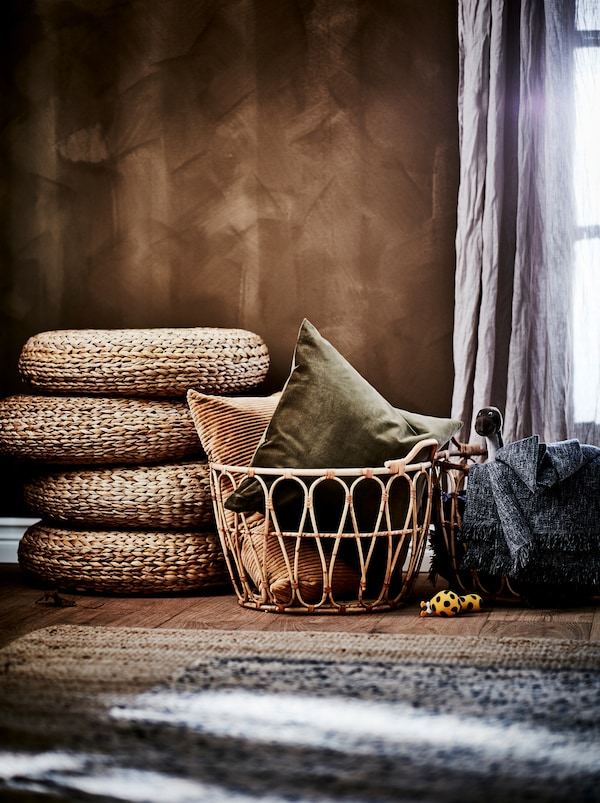 Bedroom section in an earthy-brown colour scheme: brown wall, SNIDAD rattan basket, ALSEDA stools and natural-material rugs.