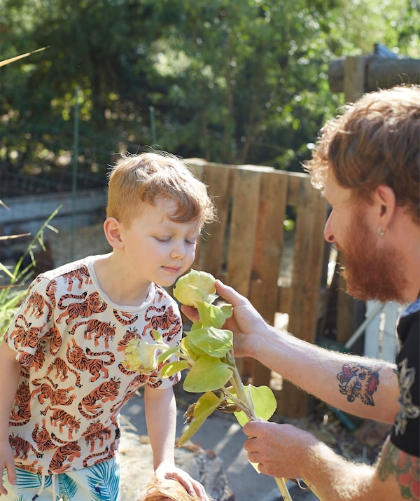 Ben helps his son smell a flower in the garden.