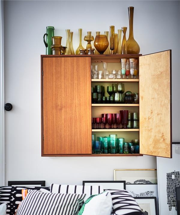 壁橱的上方和内部按照颜色分类摆放着玻璃花瓶。