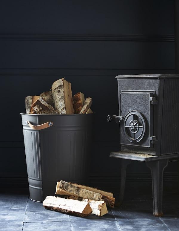 壁炉旁,带有皮革把手的 KNODD 克诺德 垃圾桶里装着木柴。