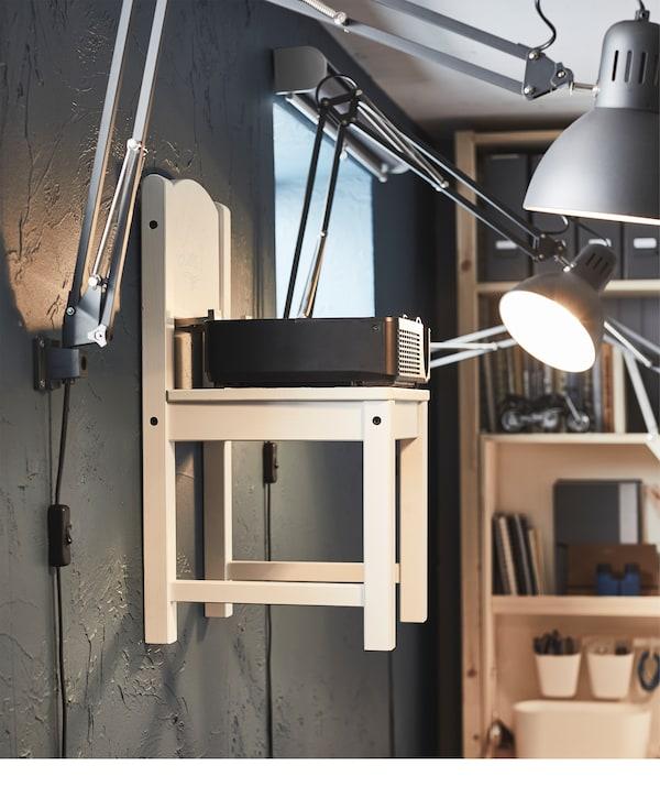 壁装挂钩上挂着儿童椅。椅子周围是壁灯,椅子上放着投影仪。
