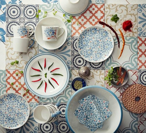 边缘带蓝色线条的米白色陶瓷盘。用红辣椒和青辣椒装饰。