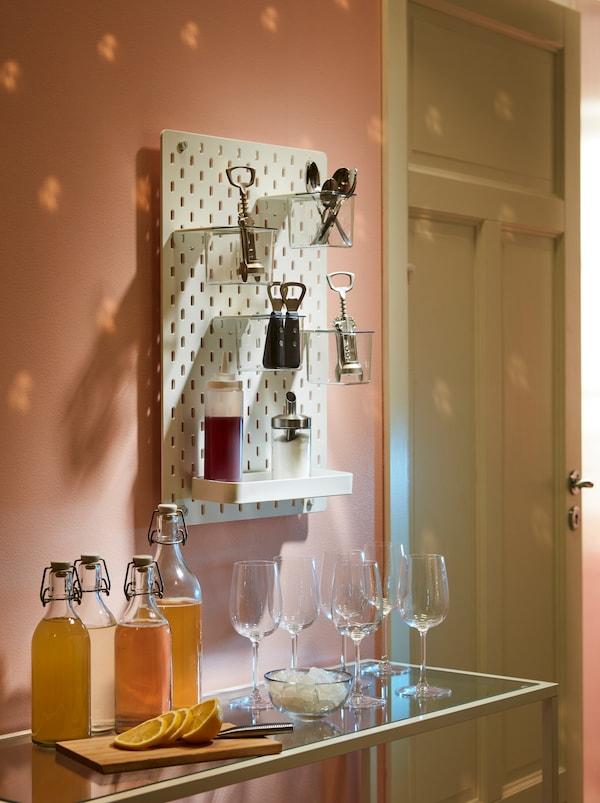 边桌上摆放着欢迎客人的饮料。上方的 SKÅDIS 斯考迪斯 钉板放有 IDEALISK 艾迪利斯 开塞钻和其他配饰。