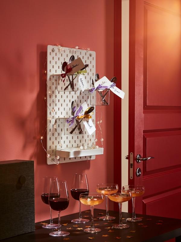 边桌上的迎宾饮料。上方悬挂着装饰钉板,钉板上摆放着 DRAGON 加肯 匙,每个汤匙上都饰有蝴蝶结和姓名标签。