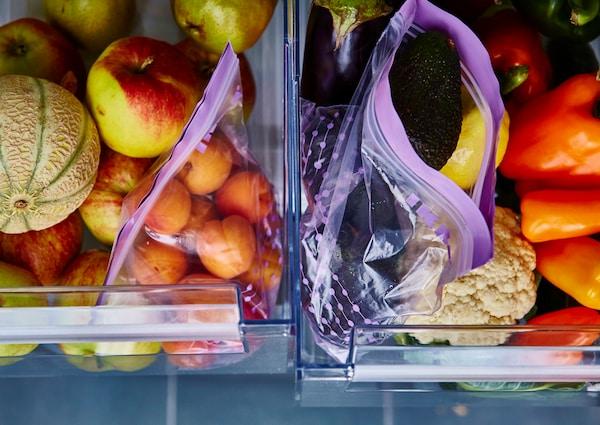 冰箱的两层抽屉打开着,里面放有已分类的果蔬。