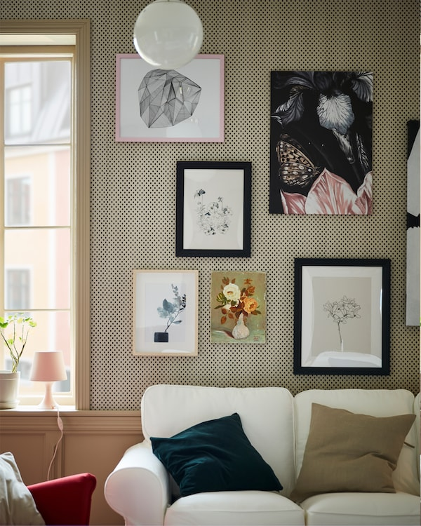 Black stained frames are combined with more frames to create a picture wall behind a white EKTORP sofa.