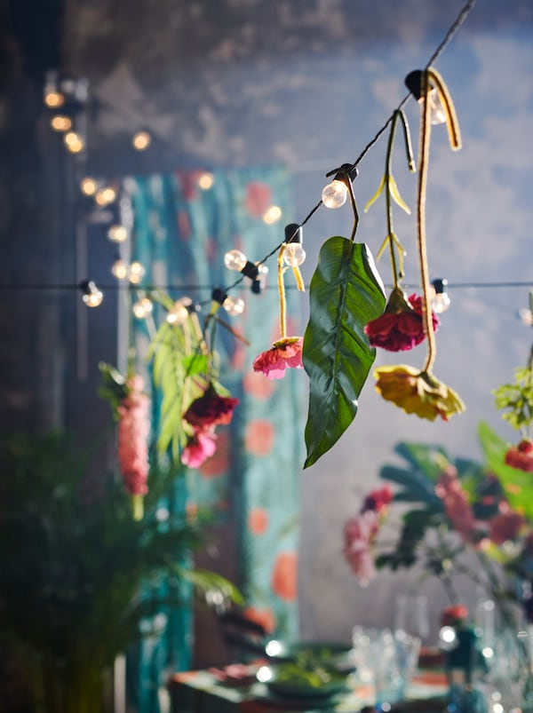 BLÖTSNÖ lighting chain with lone SMYCKA artificial flowers hanging at intervals from it, strung over a decorated set table.
